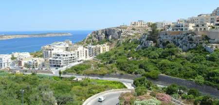 View of the village facing the sea, where on the left there is the popular sandy beach called Ghadira bay.